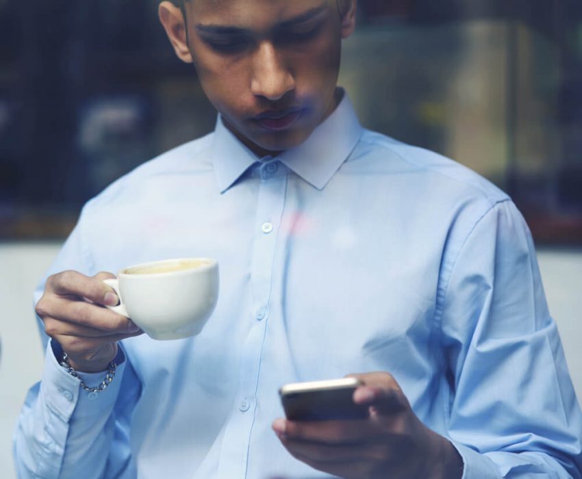 man reading phone over coffee