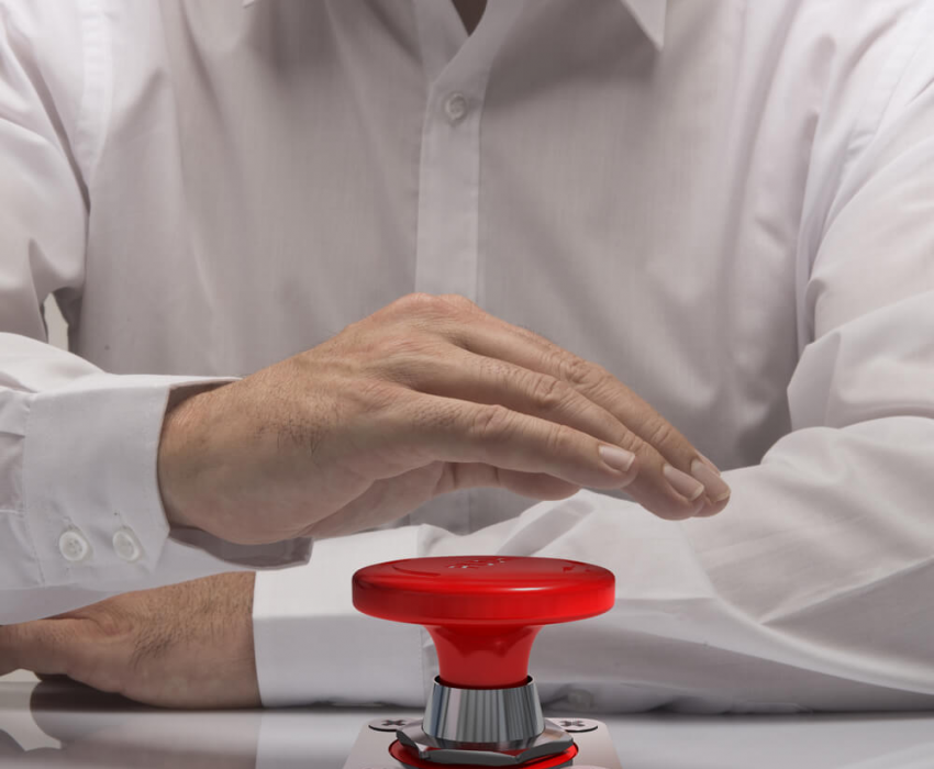 man holding hand over red button