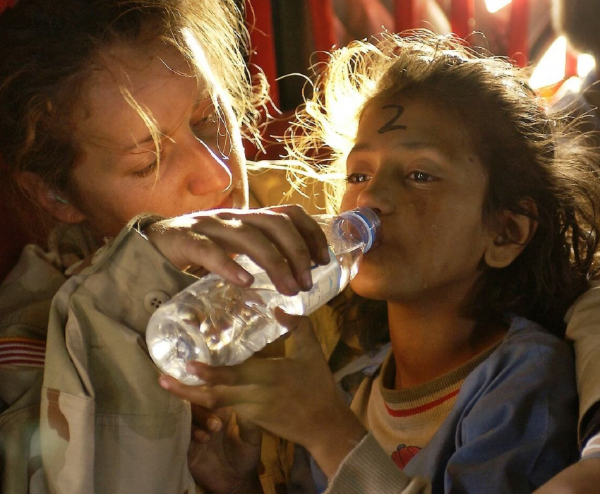 humanitarian giving bottled water to little girl